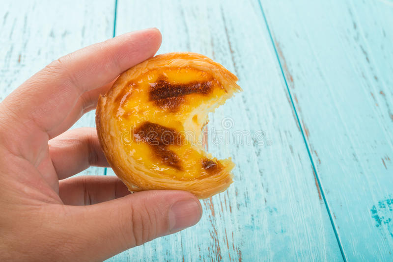 Räcka att rymma ett portugisiskt ägg syrligt med en tugga på trä fotografering för bildbyråer