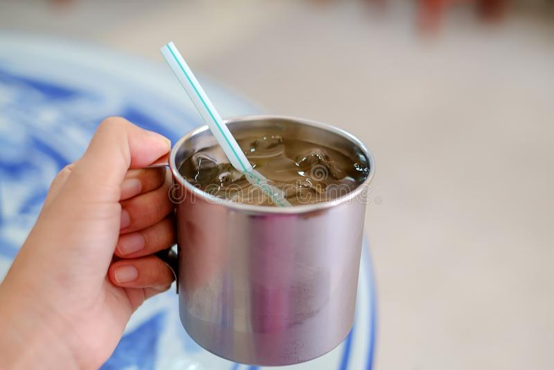 Räcka att rymma ett rostfritt exponeringsglas av rent vatten och is med en stra arkivbild