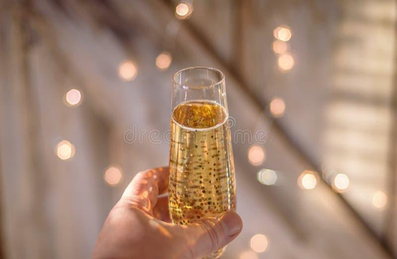 Räcka att rymma upp ett enkelt exponeringsglas av champagne med glimtljus royaltyfria bilder