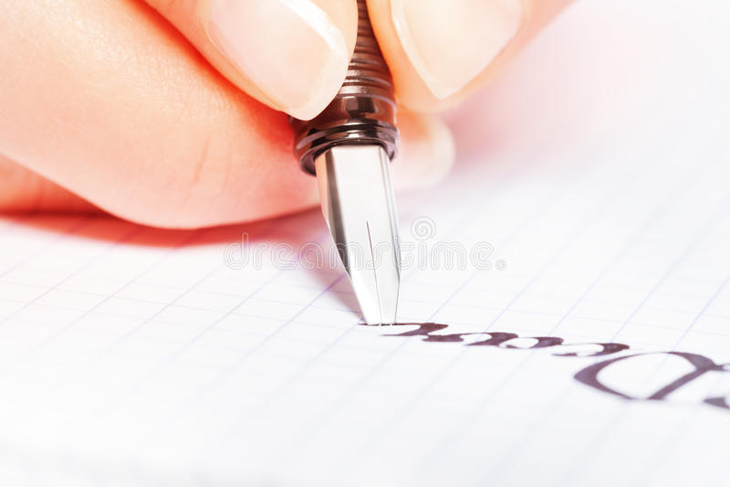 Räcka att skriva ordraringen med pennan på grafblocket royaltyfri foto