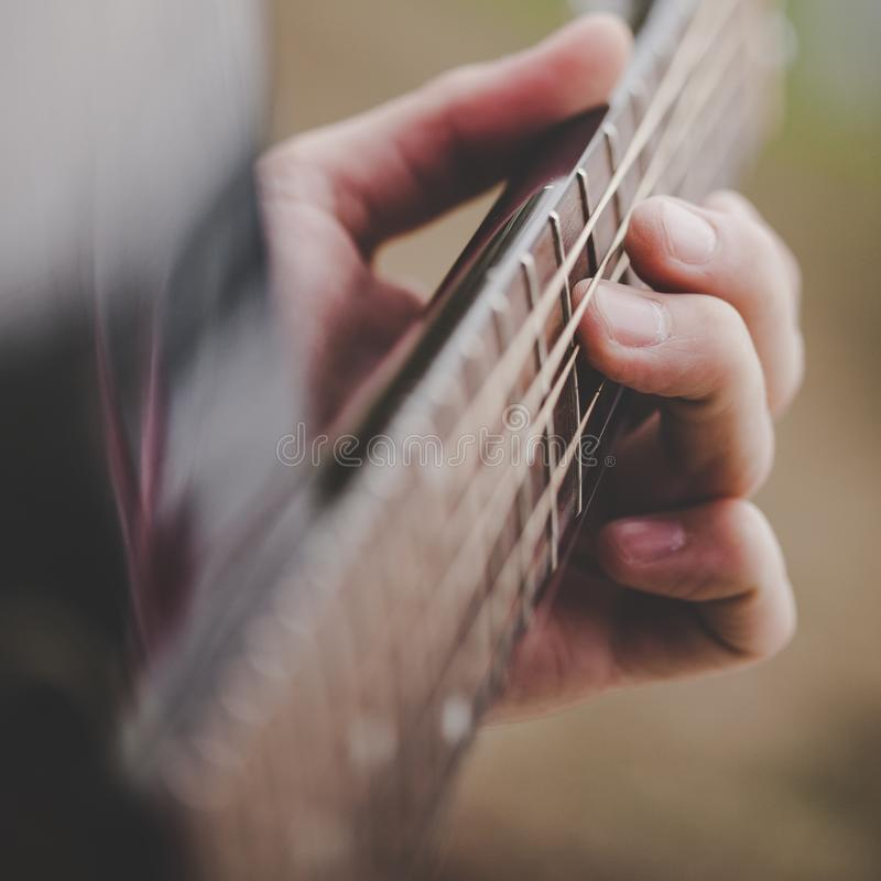 Räcka att ta ett ackord på den akustiska gitarren - nära övre royaltyfria bilder