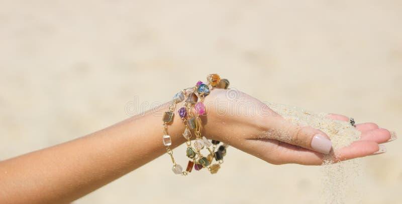 Räcka att tappa sand mellan fingrarna med det crystal armbandet royaltyfria bilder