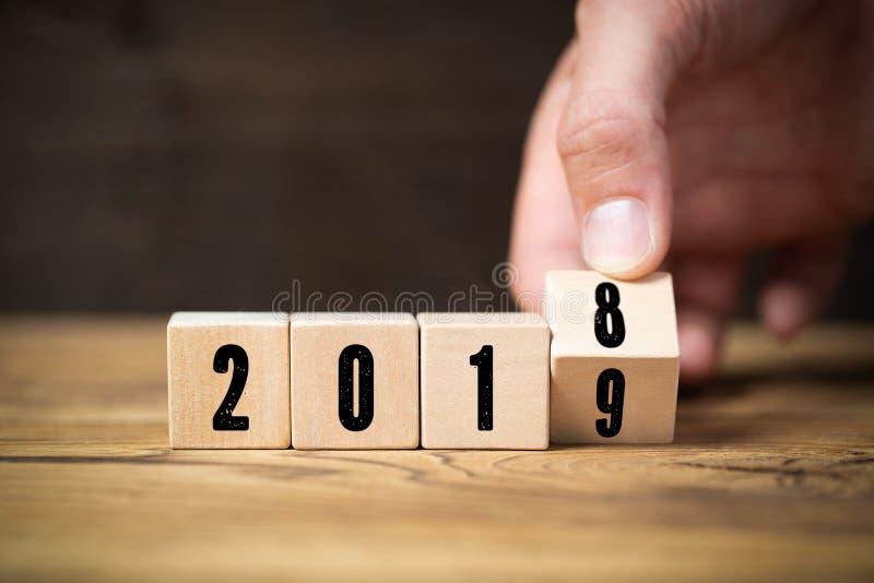 Räcka bläddring av en kub, symbolizng ändringen från 2018 till 2019 arkivbild
