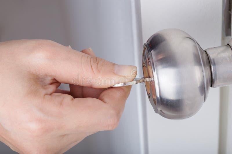 Räcka bruk tangenten för att låsa dörrknoppen på den vita dörren upp royaltyfria foton
