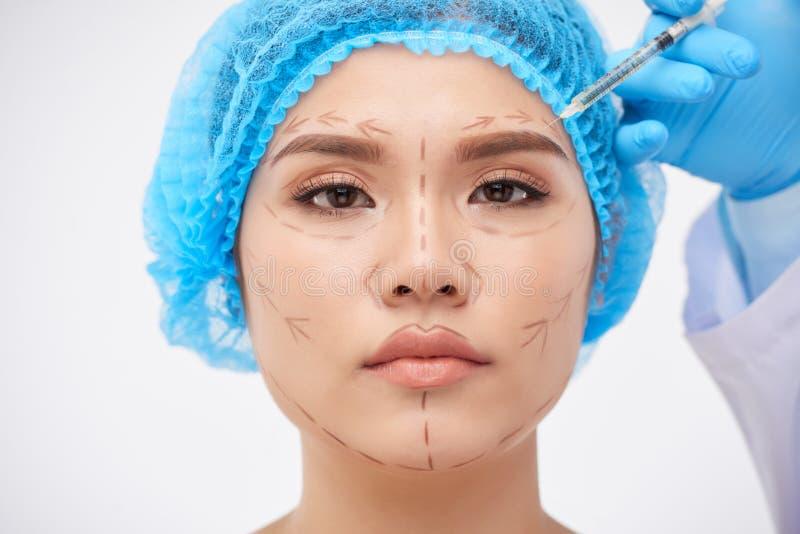 Räcka danandeinjektionen till kvinnan som förbereder sig till kirurgen arkivfoto