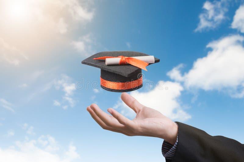 Räcka den hållande avläggande av examenhatten på bakgrund för blå himmel arkivbilder