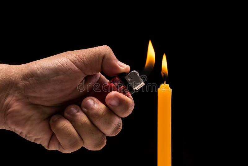 Räcka den hållande brinnande gaständaren till den ljusa stearinljuset Studioskottet är arkivfoto