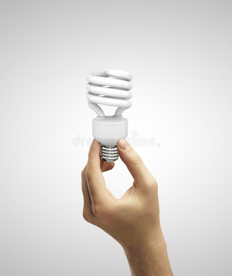 Räcka den hållande e-lampan royaltyfria bilder