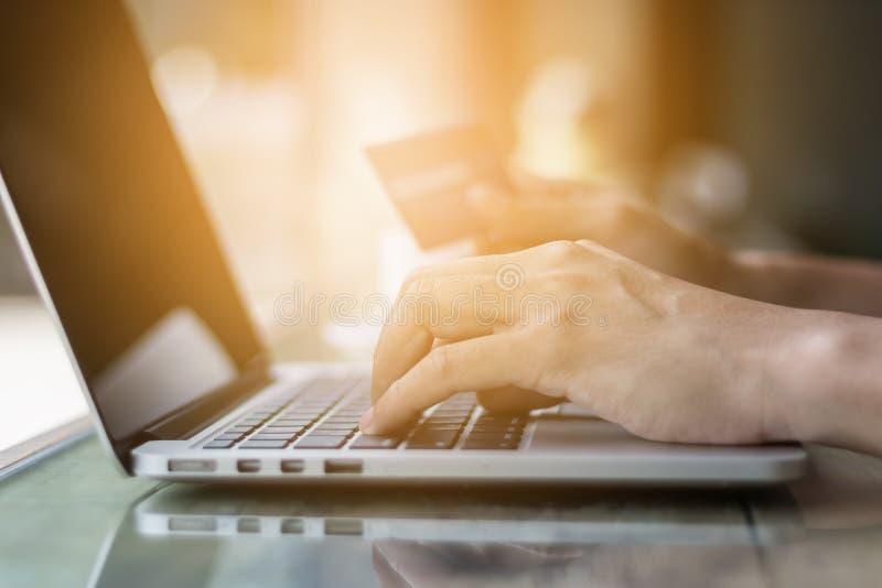 Räcka den hållande kreditkorten för online-shopping på bärbar datorecommerce arkivfoton