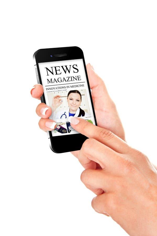 Räcka den hållande mobiltelefonen med nyheternatidskriften som isoleras över vit royaltyfria bilder