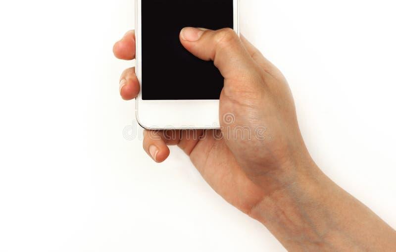 Räcka den hållande mobiltelefonen som trycker på med tummen på skärmen royaltyfria bilder