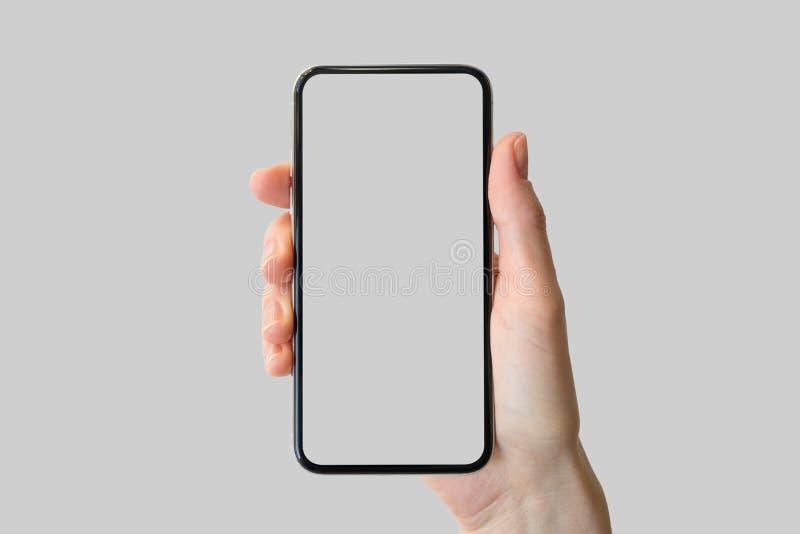 Räcka den hållande skyddsram-fria/frameless moderna smartphonen som är främst av neutral bakgrund royaltyfria foton