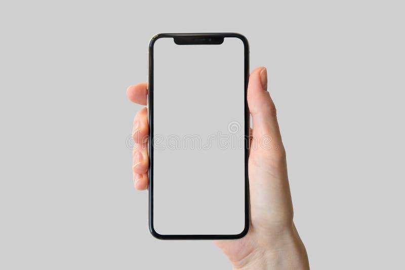 Räcka den hållande skyddsram-fria/frameless moderna smartphonen som är främst av neutral bakgrund arkivfoton