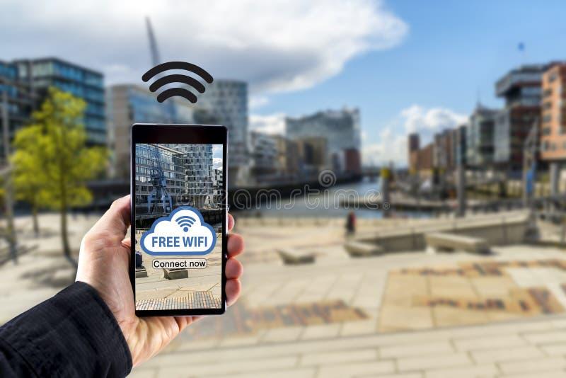 Räcka den hållande smartphonemobila enheten med staden i bakgrund royaltyfri fotografi