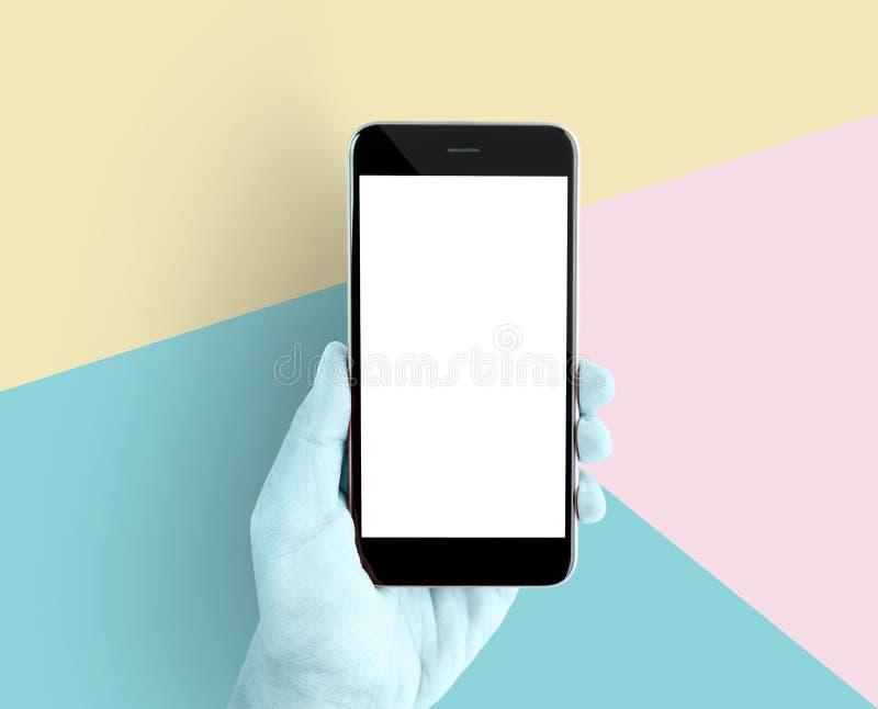 Räcka den hållande smartphonen den tomma skärmen på pastellfärgad bakgrund av blått, rosa färger, guling Teknologibegreppet är hä royaltyfri foto