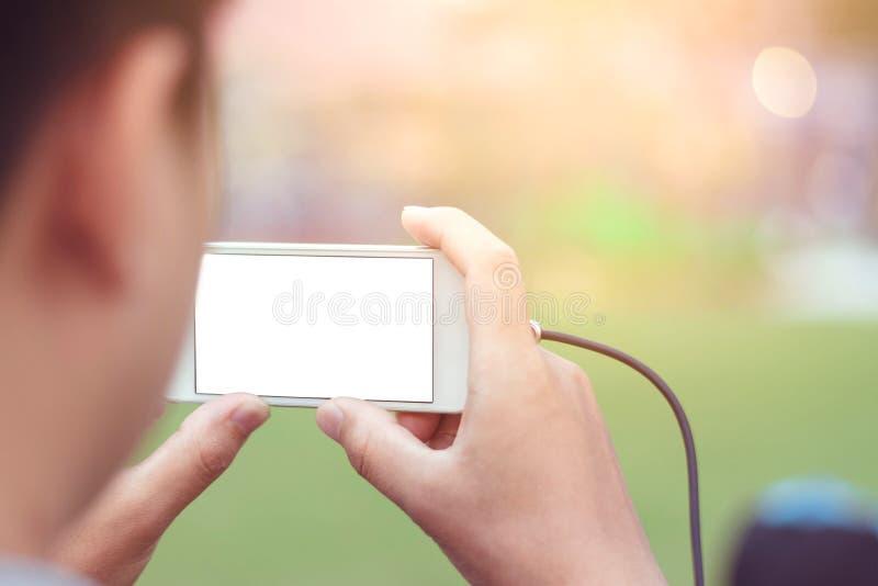 Räcka den hållande smartphonen för tar fotoet på abstrakt bakgrund royaltyfria foton