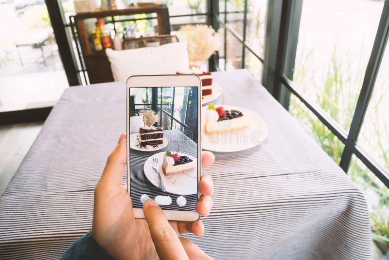 Räcka den hållande smartphonen och tafotoet av mat arkivbild