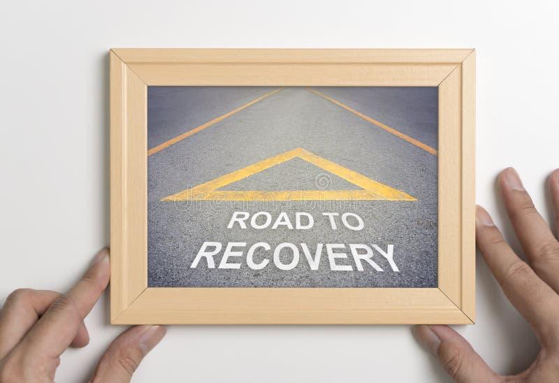 Räcka den hållande träramen med vägen till återställningsbegreppet arkivbild