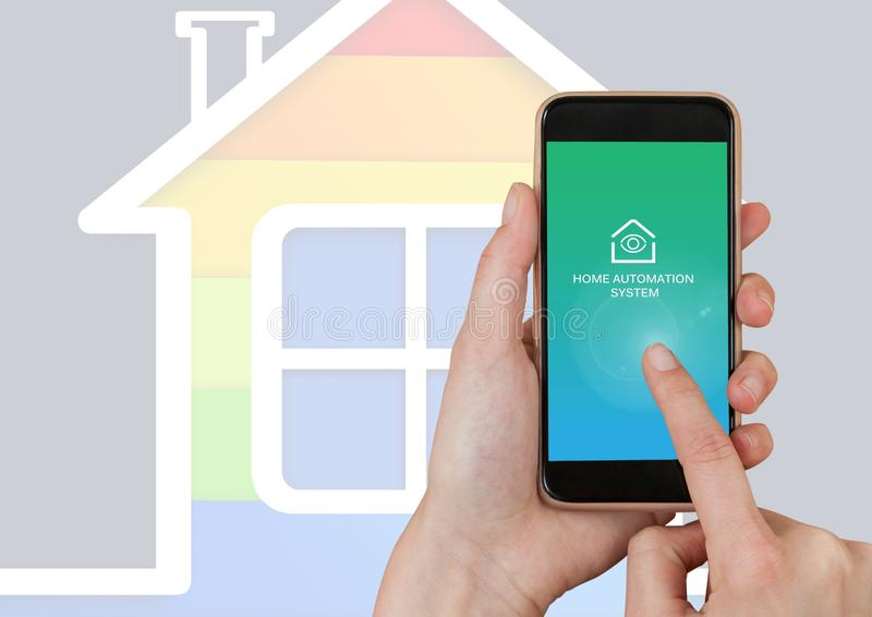 Räcka den rörande mobila ohonen med manöverenheten för systemet App för hem- automation royaltyfri foto