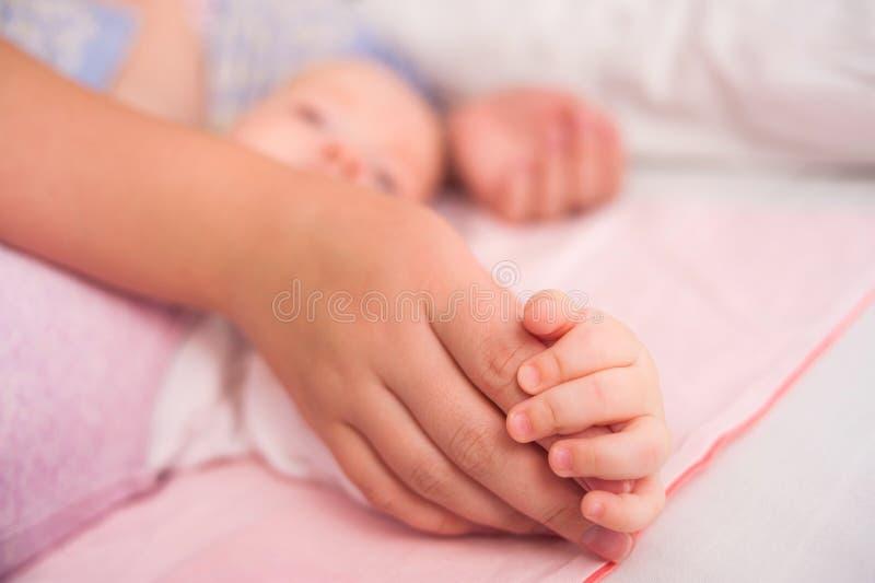 Räcka den sova caucasianen behandla som ett barn i handen av moderslutet upp Ny familj och att behandla som ett barn skydd från m arkivfoton