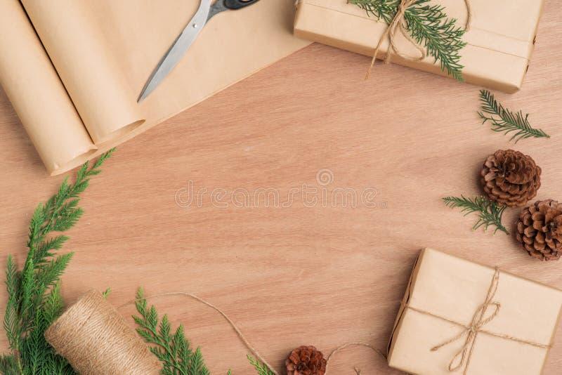 Räcka den tillverkade julklappgåvaasken och hjälpmedel på träbac arkivfoton