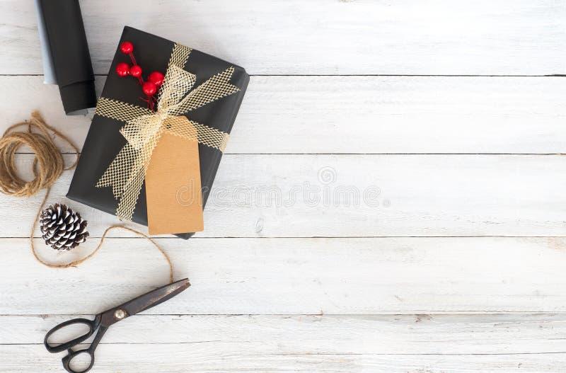 Räcka den tillverkade julklappgåvaasken och hjälpmedel på vit träbakgrund arkivfoton