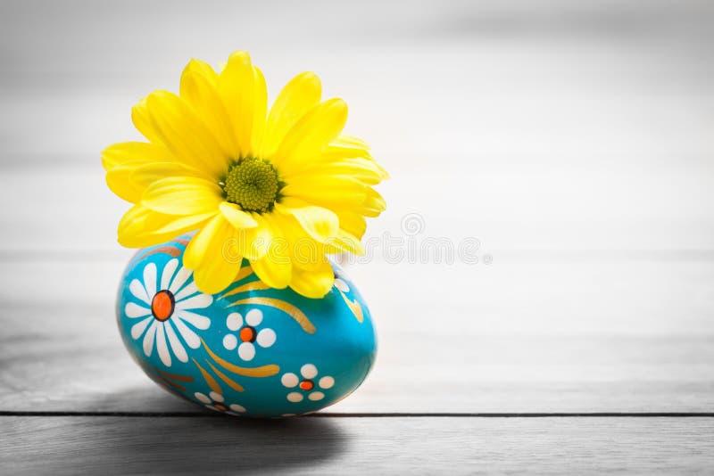 Räcka det målade påskägget och vårtusenskönablomman på trä royaltyfri fotografi