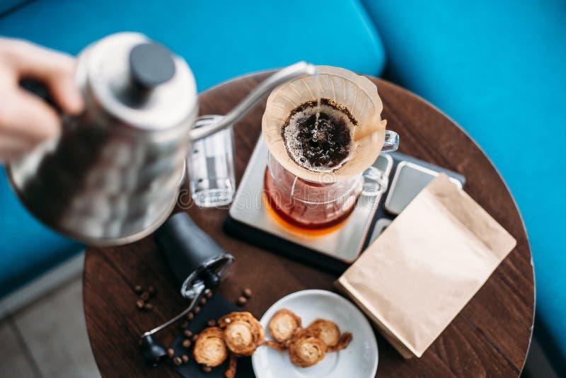 Räcka droppandekaffe, Barista hällande vatten på kaffe som malas med fi royaltyfri foto