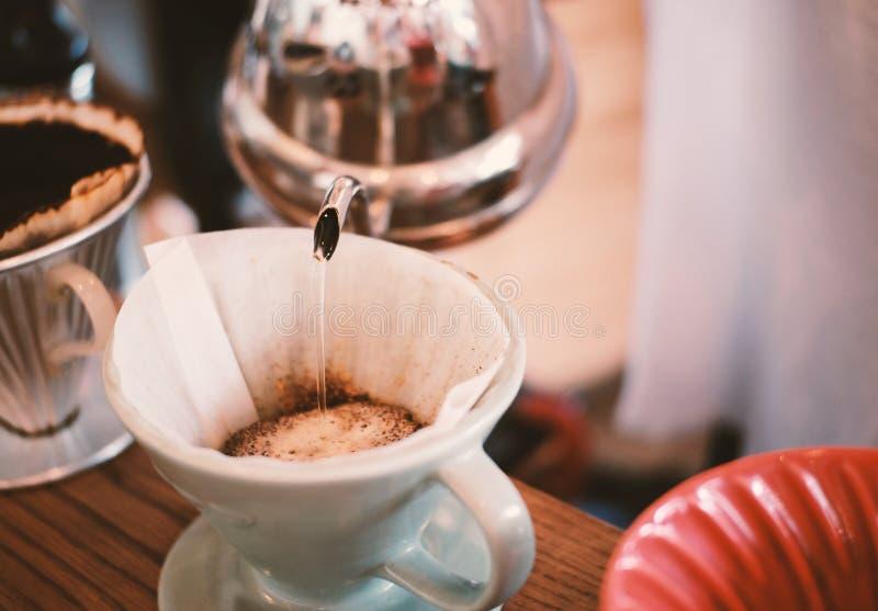Räcka droppandekaffe, hällande vatten för barista på kaffejordning arkivfoto