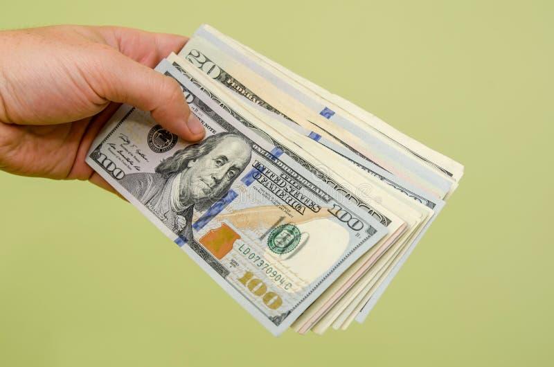 Räcka en räkning för dollar 100 till tittaren royaltyfri foto