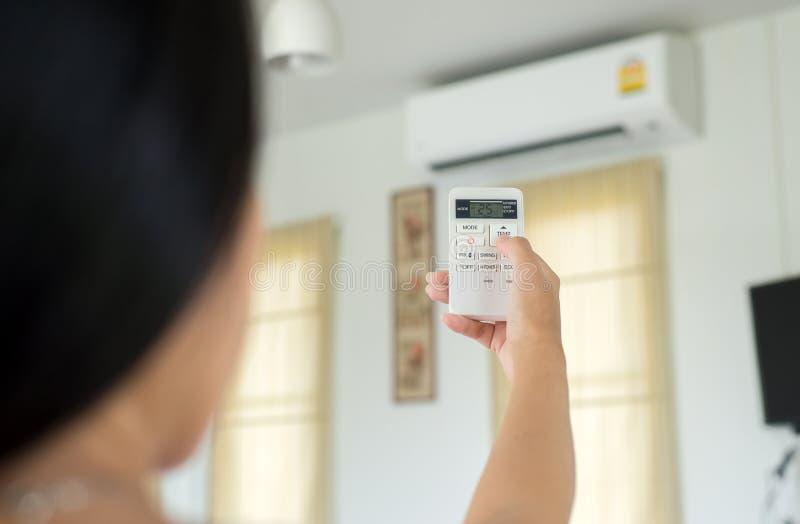 Räcka genom att använda en fjärrkontroll till att aktivera och ändra att betinga för temperaturluft royaltyfri fotografi