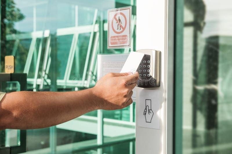 Räcka genom att använda säkerhet scanningen för det nyckel- kortet för att öppna dörren till att skriva in privat byggnad Hem- oc arkivfoton