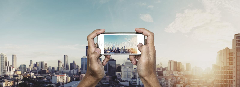Räcka genom att använda smartphonen som tar fotoet av den Bangkok staden i soluppgång arkivbild