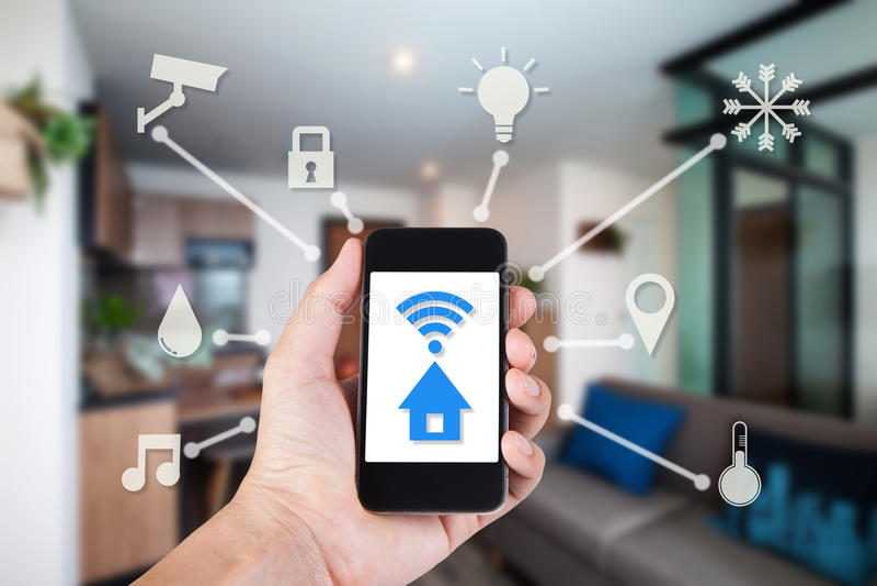 Räcka genom att använda smartphonen vid det smarta hemmet för app på mobil arkivbild