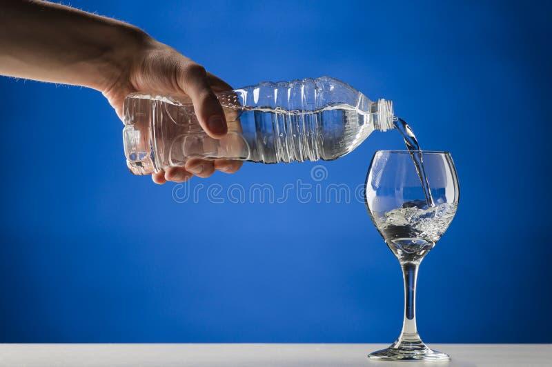 Räcka hällande rent vatten in i ett stemmed exponeringsglas arkivbild