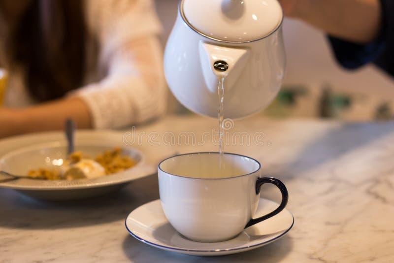 Räcka hällande te från tekannan in i tekoppen royaltyfri bild