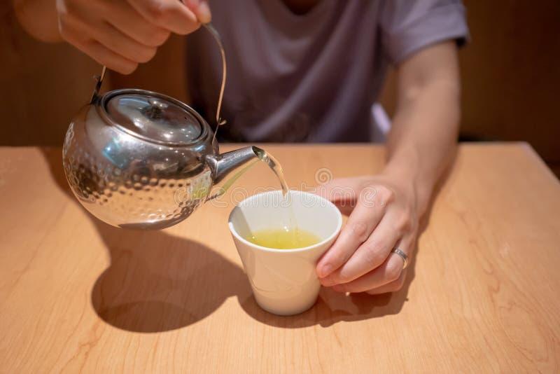 Räcka hällande varmt japanskt grönt te från silvermetalltekannan royaltyfria bilder