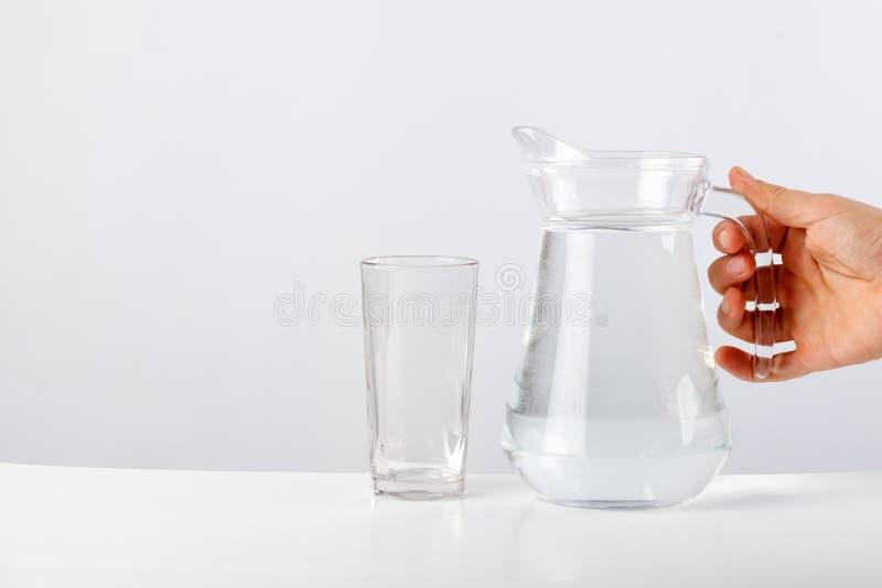 Räcka hällande vatten från den glass tillbringaren till exponeringsglas mot vit bakgrund fotografering för bildbyråer