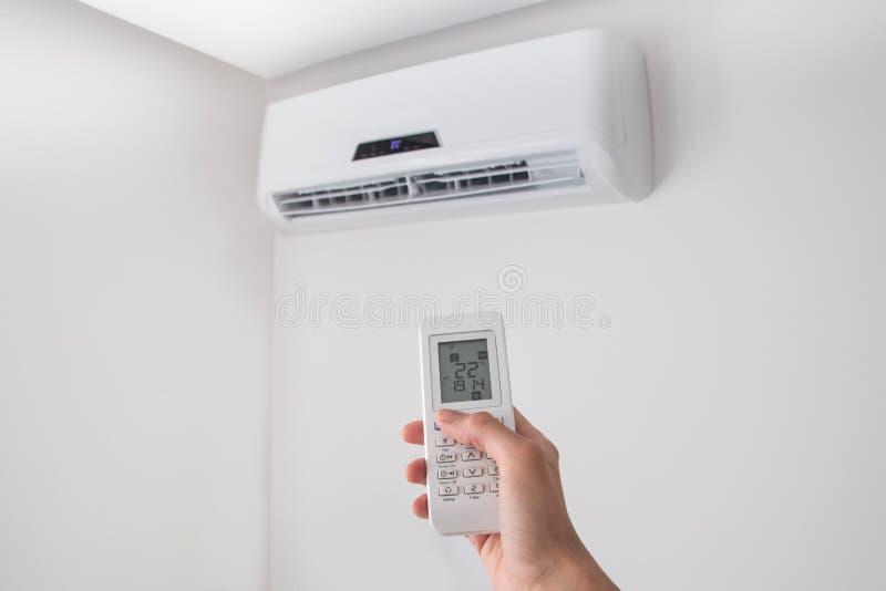 Räcka hållande fjärrkontroll för luftkonditioneringsapparat på den vita väggen royaltyfria foton