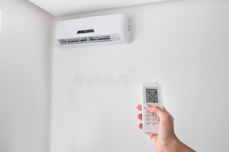 Räcka hållande fjärrkontroll för luftkonditioneringsapparat på den vita väggen royaltyfri bild