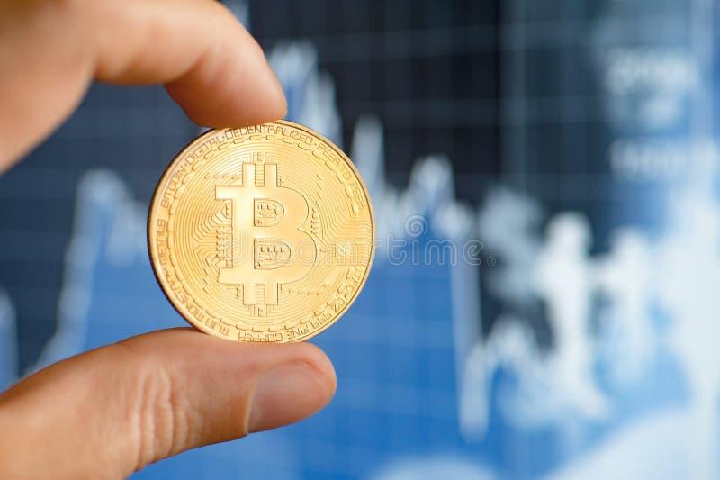 Räcka hållande guld- Bitcoin mot bakgrunden av materielcitationstecken fotografering för bildbyråer