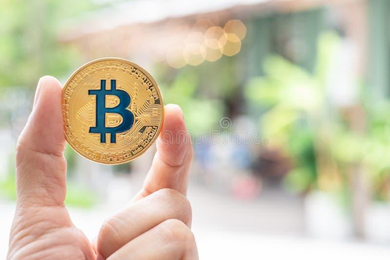 Räcka hållande guld- bitcoin som är främst av restaurang det accepterade b royaltyfria foton