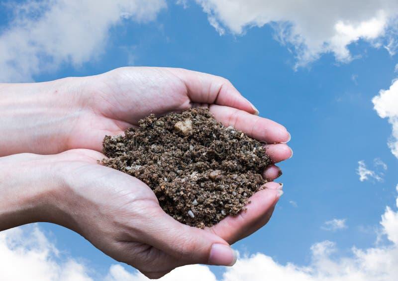 Räcka hållande jord, handen som är smutsig med jord arkivbild