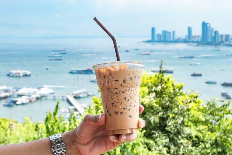 Räcka hållande med is kaffe och havet med många fartyg royaltyfria bilder