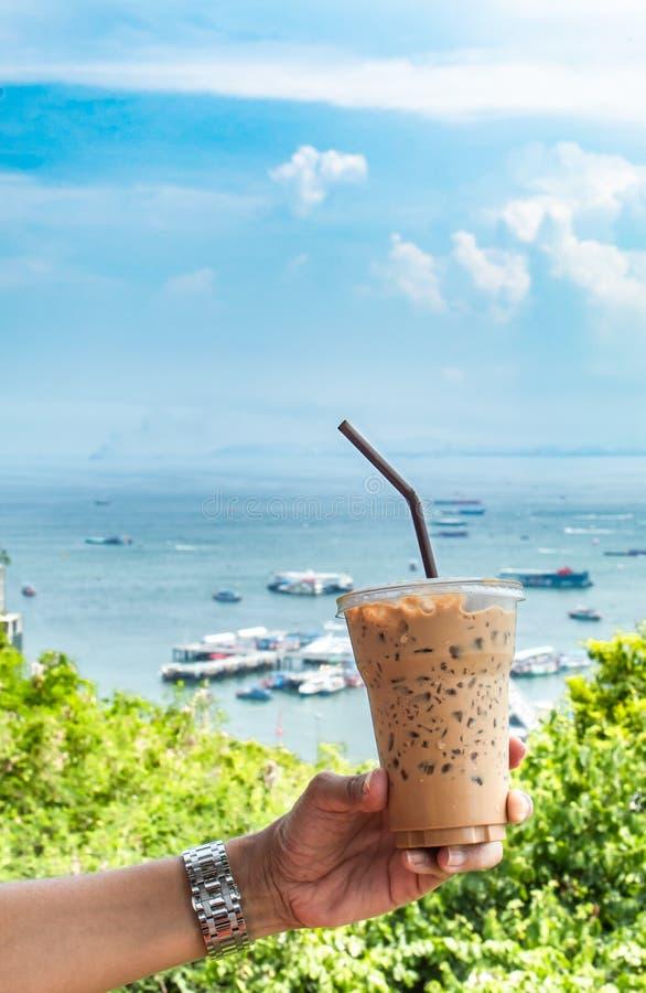 Räcka hållande med is kaffe och havet med många fartyg arkivbilder