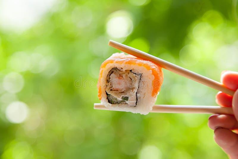 Räcka hållande pinnesushirulle med den röda fisken på naturlig bakgrund för sommar arkivbild
