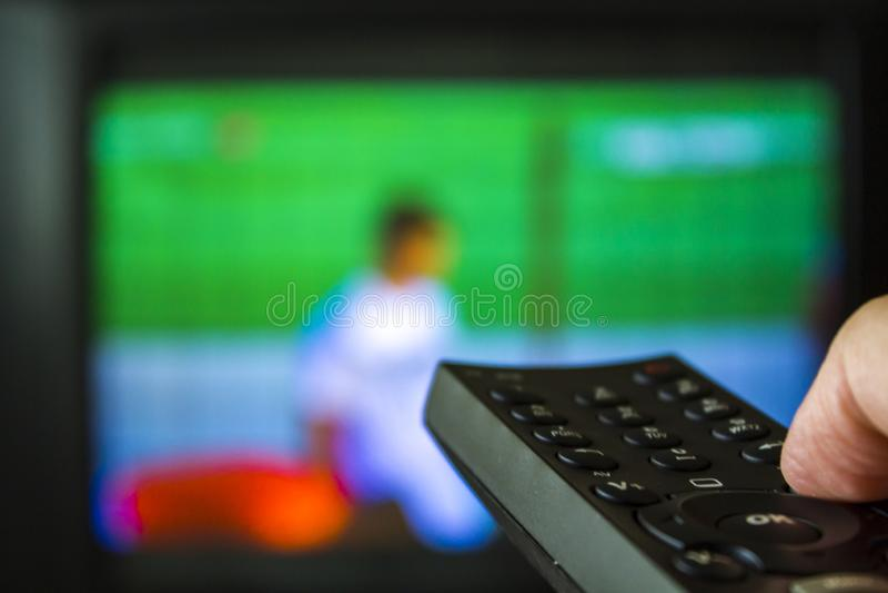 Räcka hållande TVfjärrkontroll med tv på bakgrunden arkivbild