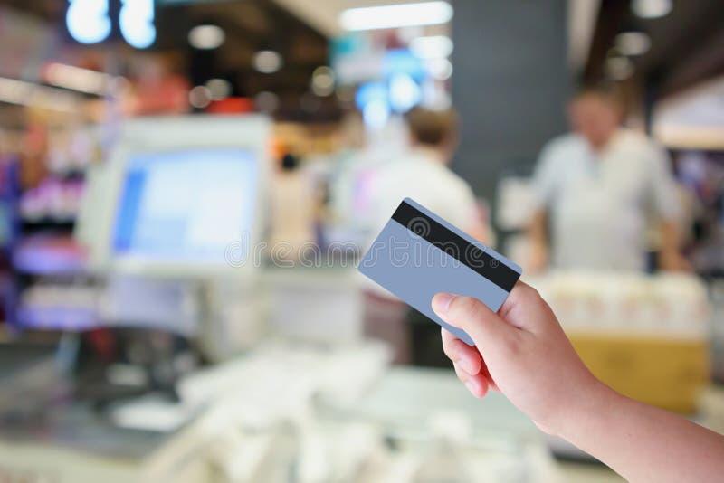 Räcka hållkreditkorten med räknaren för supermarketkassörskakontrollen royaltyfria bilder