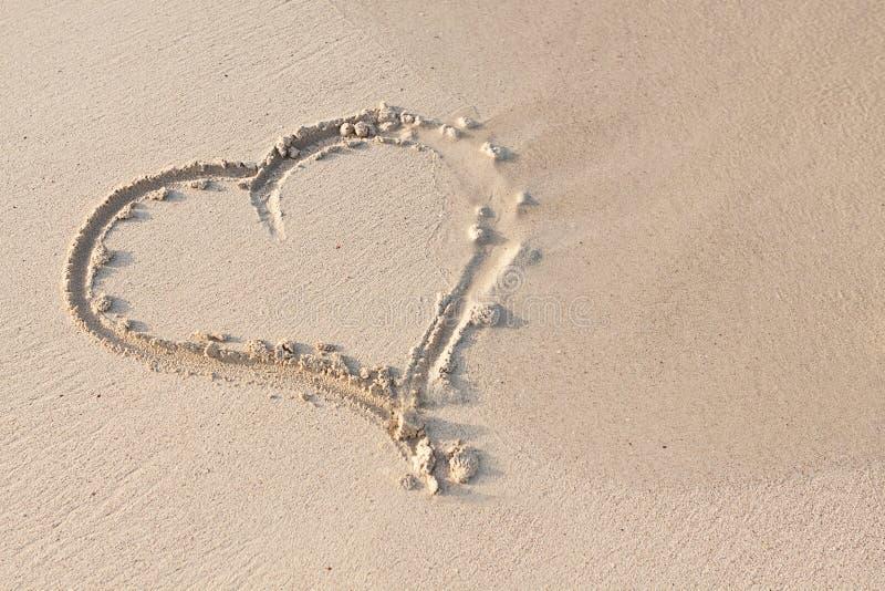 Räcka handstil i sand i sommarferier på stranden royaltyfri foto