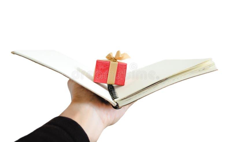 Räcka innehavet öppnade anteckningsboken med den lilla gåvaasken inom, isolerat på vit bakgrund royaltyfri fotografi